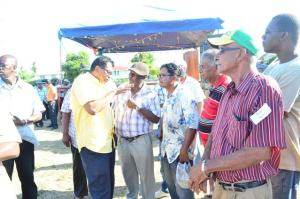 Minister of Public Security Khemraj Ramjattan in discussion with residents prior to the commencement of the community meeting at Whim, Corentyne, Berbice