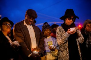 Randolph Holder Sr., the father of the slain officer killed in East Harlem last week, with Sherry Holder, the officer's sister, second from right, at a vigil in Richmond Hill, Queens, on Saturday.