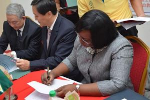 Chinese Ambassador Mr Zhang Limin and Minister within the Ministry of Public Health Dr. Karen Cummings exchanging documents