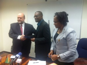 Minister of Public Infrastructure, David Patterson (center) and US Ambassador. Perry Holloway after signing the MoU.