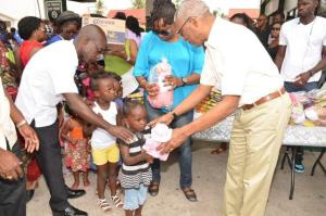Little girls queue up to receive a Christmas gift from President David Granger in Buxton