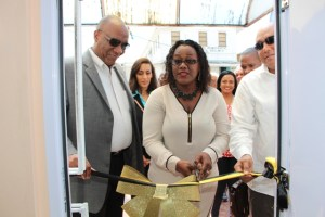 Minister Simona Broomes cuts the ribbon to recommission the GGB's Bartica Office while Ministers Harmon and Trotman look on.