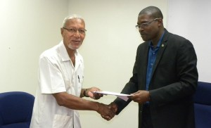 Minister of Public Infrastructure, David Patterson (right) hand over the agreement to Chairman of the Berbice Bridge Company Incorporated (BBCI), Egbert Carter