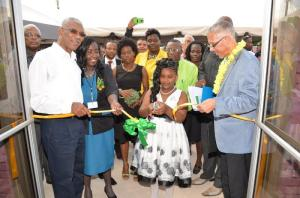 President David Granger (first, left), Chief Executive Officer of LEN Ms. Valerie Patterson (second,left) and Minister of Business Dominic Gaskin hold the ceremonial ribbon as Linden resident Rebecca Austin cut it to declare open the newly recommissioned LEN office.