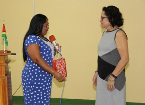 First Lady Mrs. Sandra Granger smiles warmly as she is presented with a token of appreciation from Tarmattie Ralph from the Rupununi Chambers of Commerce and Industry (RCCI)