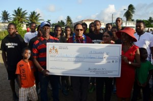 Prime Minister Moses Nagamootoo and Wife Sita Nagamootoo hands over the cheque to Founder of the Group Beryl Haynes in the presence of the community members.