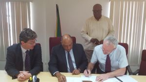 Mr. John McKenna of Tullow Oil signs the Agreement as Minister of Natural Resources, Mr. Raphael Trotman (centre), British High Commissioner to Guyana, Mr. Greg Quinn (first, left) and Mr. Newell Dennison, acting Commissioner, GGMC (standing) look on.
