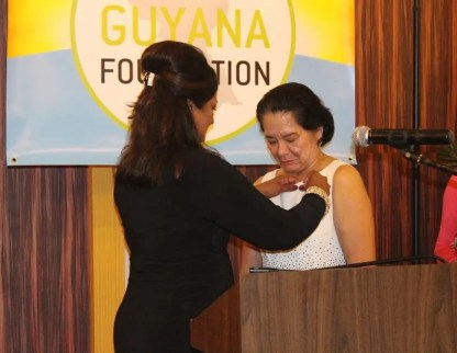 Founder of the Guyana Foundation, Ms. Supriya Singh-Bodden, adorns First Lady, Mrs Granger with a pin, during the installation ceremony