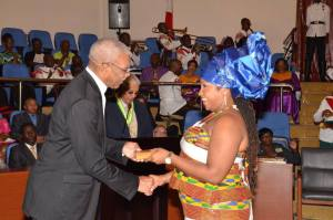 Aisha Jean Baptiste receives the Medal of Service on behalf of the African Cultural and Development Association from President David Granger.