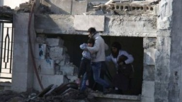 A child is evacuated from the damaged hospital in Azaz (AP photo)