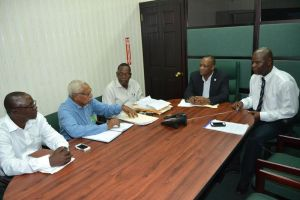 Minister Harmon being briefed by the probe team yesterday