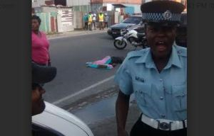A policewoman at the scene reacts to the cruel death of the man, seen lying on the road behind