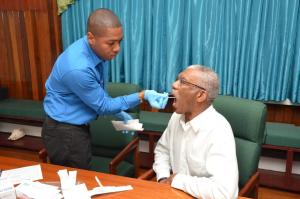 President David Granger allows the painless removal of the sample for his Ancestry DNA test by Mr. Shawn Manbodh, Quality Manager and Medical Technologist, which was done at State House, this morning.