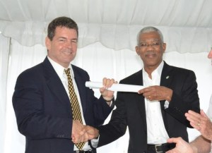 President David Granger handing over a congratulatory parchment signed by the Village Council of Buxton-Friendship in 1965, which details Eugene Correia's achievements