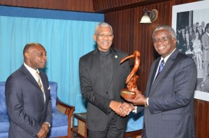 Prime Minister Freundel Stuart presents a gift to President David Granger for the people of Guyana, during a meeting at the Ministry of the Presidency