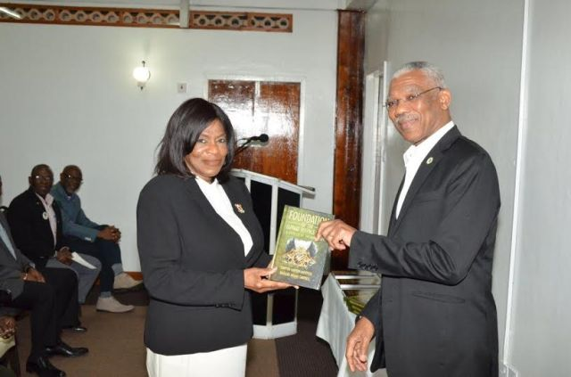 """President David Granger receives his copy of the book  """"Foundation of the Guyana Defence Force-A Soldier of Valour Story"""" from co-author, Ms. Khalilah Campbell"""