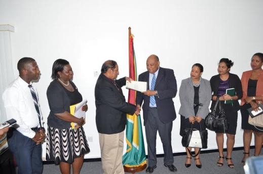 Minister  Raphael Trotman hands over the reworked draft of the Code of Conduct for Ministers, Members of Parliament and Public Office Holders to PM Moses Nagamootoo. Also in photo are members of the Sub-committee established to review and strengthen the draft code