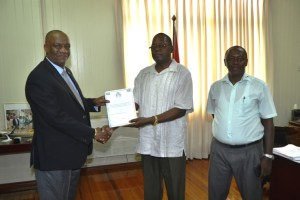 Minister of State, Mr. Joseph Harmon receives the Report into the inquiry of Guyana Oil Company Limited from Chairman of the Board of Inquiry, Mr. Winston Cosbert, while Mr. Julius Wright looks on.