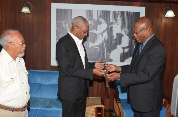Enrico Woolford handing over the sword to President David Granger at the Ministry of the Presidency. Also in picture is Chairman of the National Trust of Guyana, Lennox Hernandez