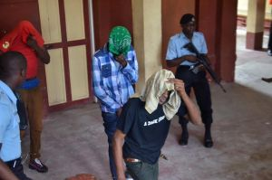 The three suspects hiding their faces from the cameras during their court appearance this morning in Georgetown