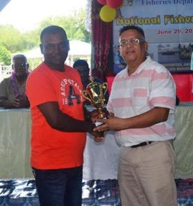 Chief Fisheries Officer, Denzil Roberts handing over a trophy to a during the Fisherfolk Day