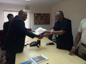 Minister Trotman receiving the COI report from Major General (rtd) Joe Singh