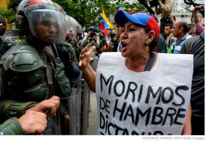 """A woman with a sign reading """"We starve"""" protests against new emergency powers decreed by President Nicolas Maduro in front of a line of riot policemen in Caracas on May 18, 2016.  (AFP photo)"""