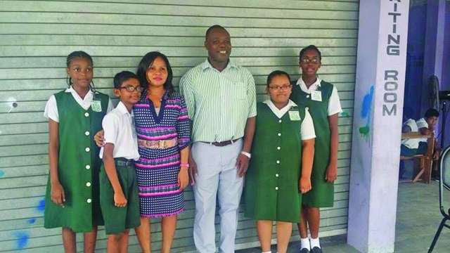 Wilfred Success and Africo Selman with the top students of Success Elementary