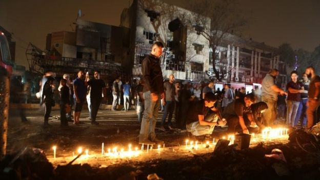Persons gathered by buildings burned out by the huge blast (AP photo)