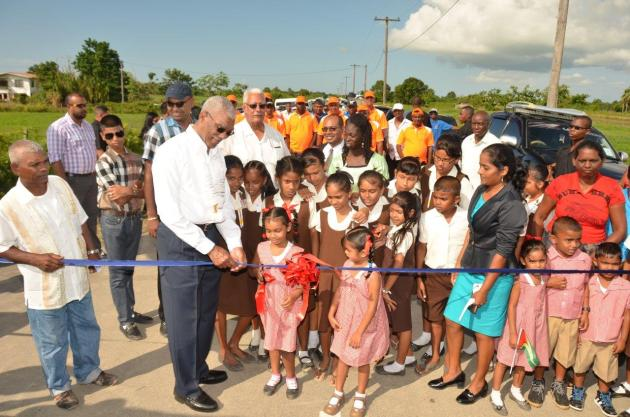 President David Granger helps this little girl cut the ribbon to mark the opening of the Ruby Paved Road, which is 7.7 km long.  This project also included a reinforced concrete bridge and culverts. (GINA photo)