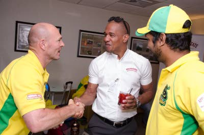 Paul Nixon (left), Jamaica Tallawahs head coach, greets Gary Dixon, marketing director of J Wray & Nephew Limited, while Kumar Sangakkara looks on during a send-off session at the Norman Manley International Airport recently. (Jamaica Observer photo)