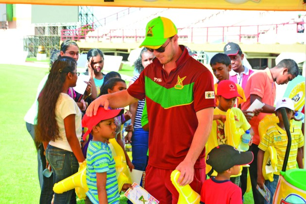 Members of the Guyana Amazon Warriors on Monday interacted with the excited children of the Shaheed's Orphanage at the Providence Stadium. In photo, star batsman Chris Lyn shares a light moment  with a young cricket fan (Dexter Ceres photo)