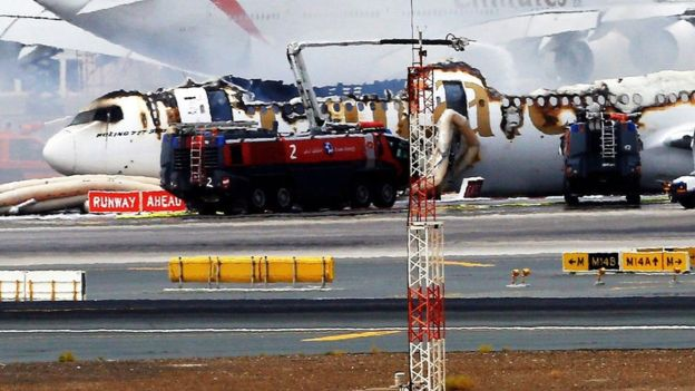 The inflatable emergency exit slides can be seen next to the remains of the aircraft (EPA photo)
