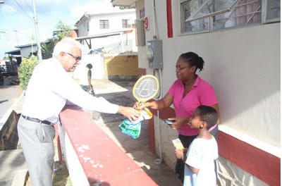 Health Minister Terrence Deyalsingh presents Maraval resident Allison Welch-Dick and her son, Khalil, with mosquito zappers during the ministry's mosquito eradication exercise yesterday in Boissierre Village, Maraval.