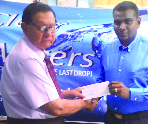 KMTC Chairman, Justice Cecil Kennard (left) receives first prize cheque from Amarjeet Hardat for the Clear Waters Race