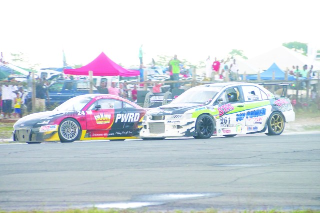 Guyana Kristian Jeffrey Mitsubishi EVO 9 (white car) on the tail of  Jamaican's Doug Gore Audi TTRS (Marceano Narine Photo)