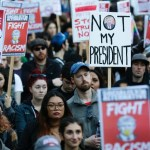 People in downtown Seattle carry signs and listen to speakers in a protest against President-elect Donald Trump..