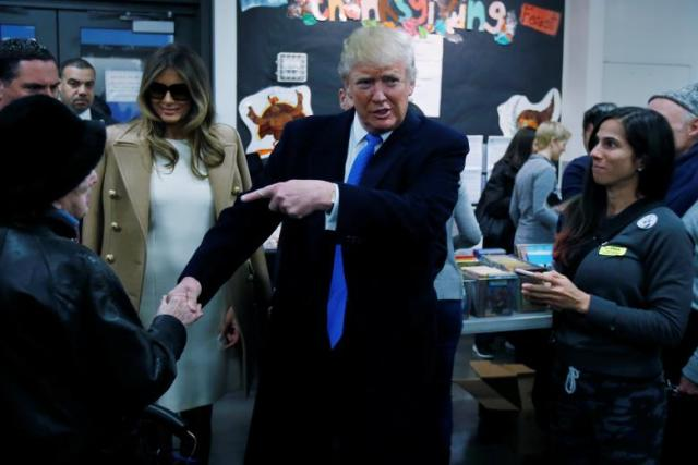 Republican presidential nominee Donald Trump shakes hands with a woman before voting at PS 59 in New York, New York, U.S. November 8, 2016. REUTERS/Carlo Allegri
