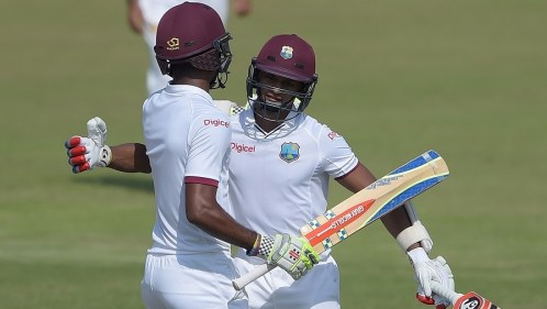 Shane Dowrich embraces Kraigg Brathwaite after securing victory on the fifth morning in Sharjah © AFP