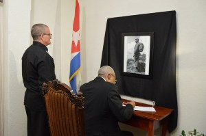 President David Granger signs the Book of Condolence as Cuban Ambassador to Guyana, Mr. Julio Cesar Gonzalez Marchante also pays his respects.