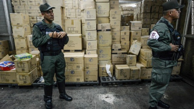 Members of the Venezuelan national guard stand next to boxes full of confiscated toys in a warehouse in Caracas on December 9, 2016.