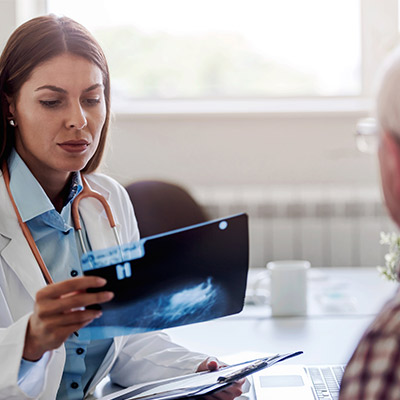 Specialist physician looking at an xray while meeting with a patient.