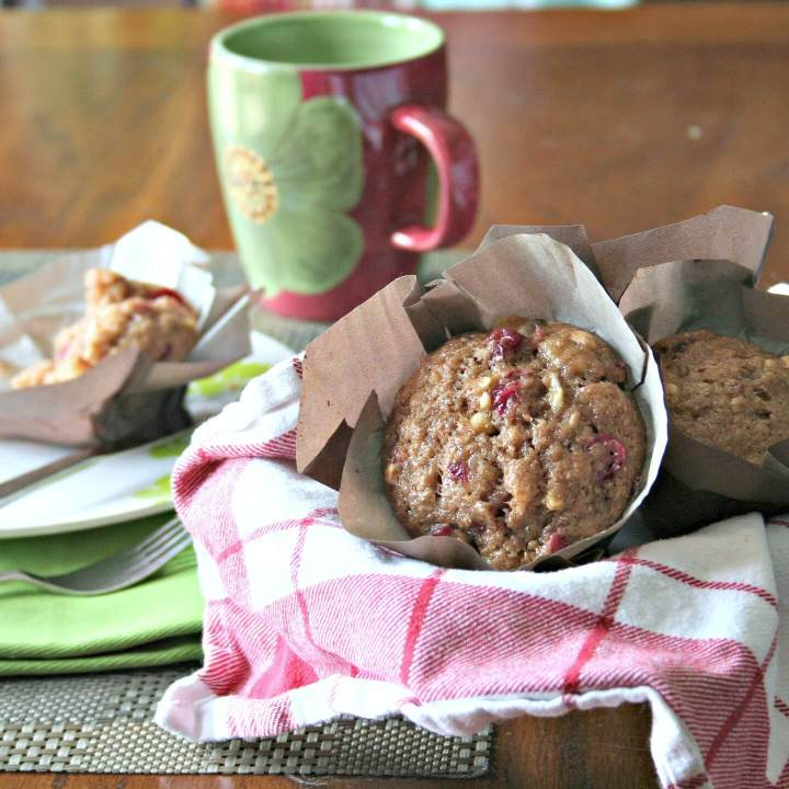cranberry cashew muffins in a red and white checked tea towel, a cup of coffee in the background