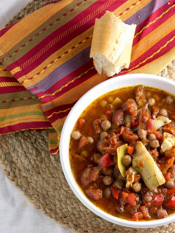 chickpea cacciatore stew with artichokes in a white bowl on a colourful napkin with a chunch of bread
