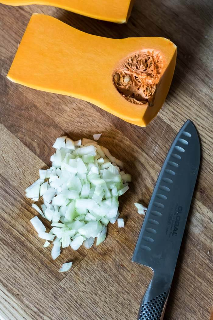 Butternut Squash cut in half with chopped onions on a cutting board
