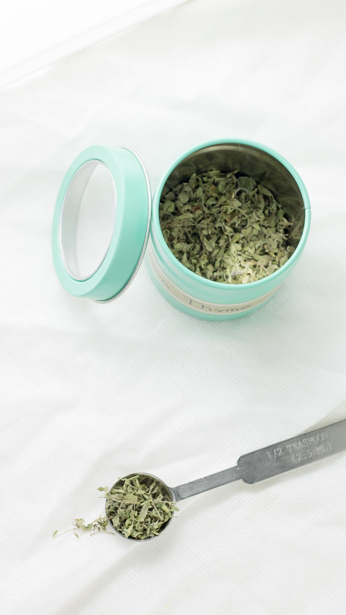 dried thyme in a blue spice jar and a teaspoon of thyme