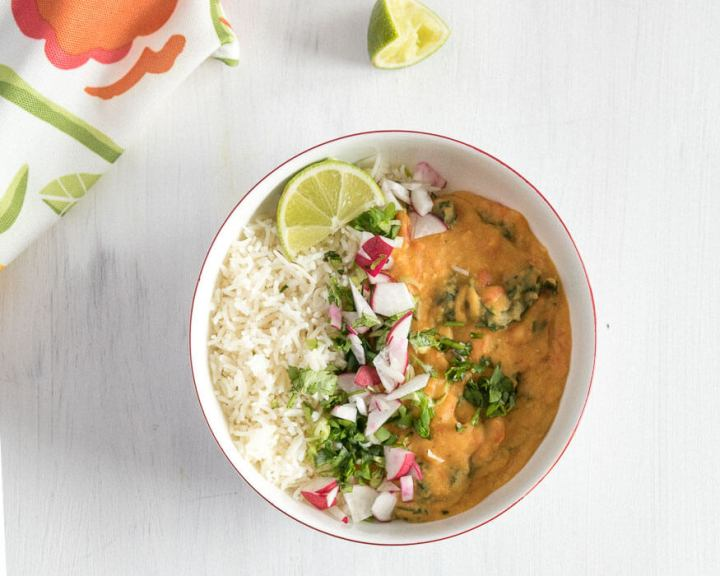 Coconut Red Lentil Curry in a bowl with rice and fresh squeesed lime.