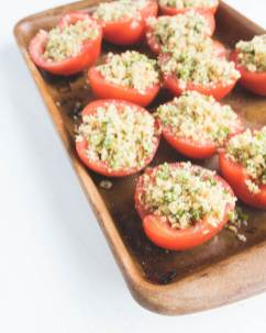 parmesan stuffed tomatoes ready for baking on a stone baking tray