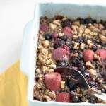 berry baked oats in a baking dish with a serving spoon and yellow napkin