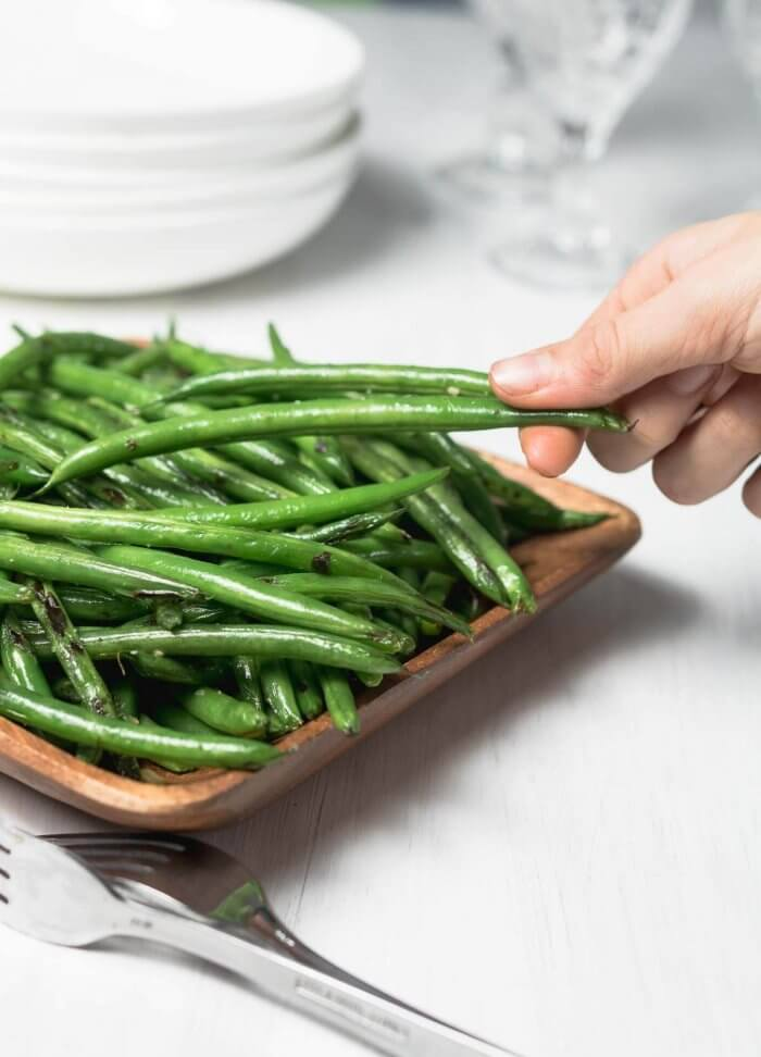 sesame green beans served, picture shows a hand stealling a few from the platter